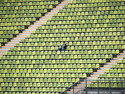 person sitting alone in green gang chair