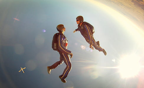 two person facing each other while skydiving