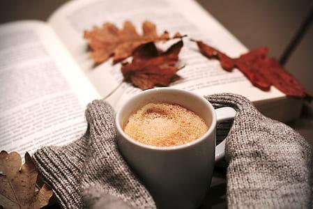 white ceramic coffee mug beside a open book