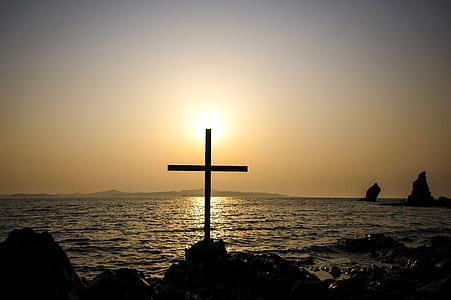 cross on rock near seashore
