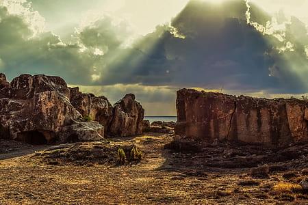 brown cliff near a sea under grey cloudy sky