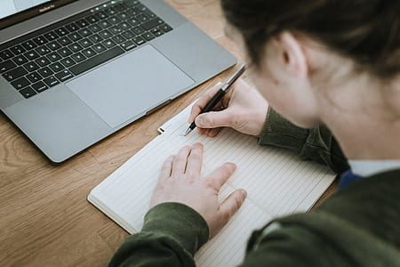 woman writing on lined paper near MacBook Pro