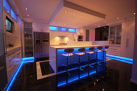 white wooden kitchen with blue LED strips surrounded on corners at night time