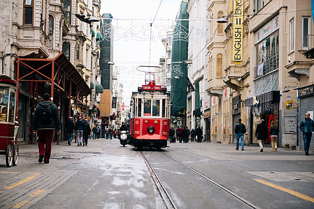 Tram traveling on road surrounded by beige commercial buildings with people walking on both sides during daytime