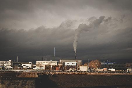 Factory releasing smoke under cloudy sky