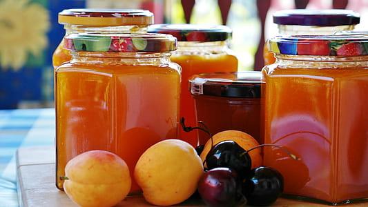 assorted fruits beside five glass mason jars