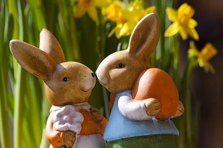 two rabbit figurines near daffodil flower