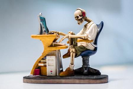 human skeleton sitting on chair in front table figure