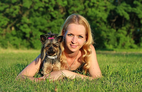 woman wearing black tank top lying on green grass field with black and tan Yorkshire terrier puppy during daytime