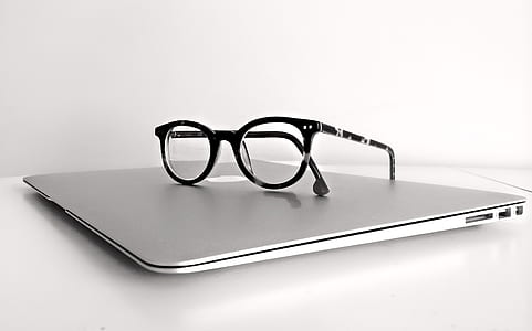 black framed clubmaster-style eyeglasses on top of MacBook Air