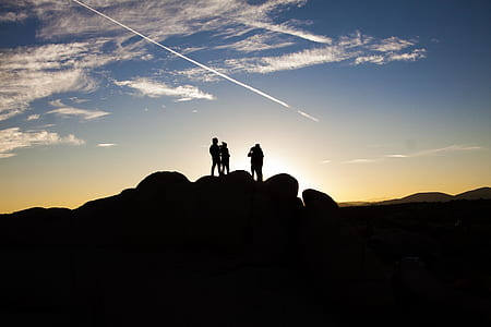 Silhouette Photo of People on Top of Rock Formation