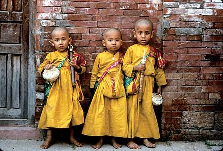 three boys wearing yellow thobes
