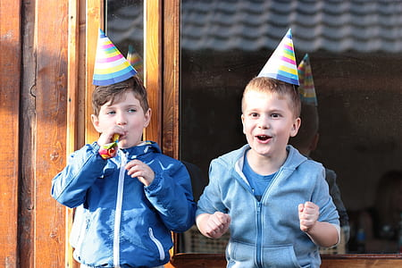 two boys wearing jackets and party cones