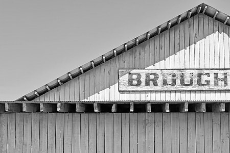 grayscale photo of a wooden signage