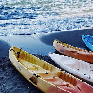 closeup photography of four kayaks in line on seashore