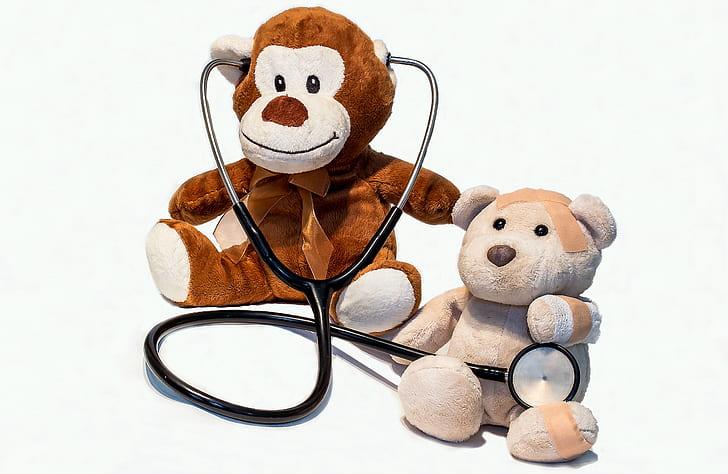 monkey plush toy wearing stethoscope sitting beside beige bear plush toy