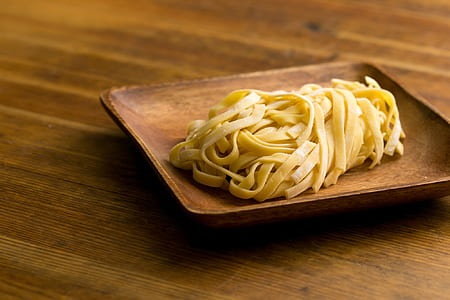 cooked flat pasta on brown wooden plate