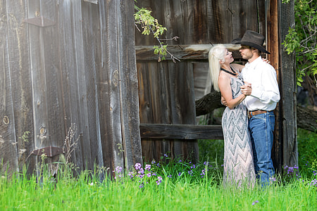 man wearing white dress shirt and black cowboy hat while holding a white haired woman