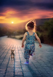 girl wearing blue and black leopard pattern overalls running toward leopard cub