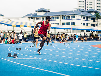 men racing on track and field at daytime