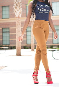 person in blue shirt and brown jeans walking