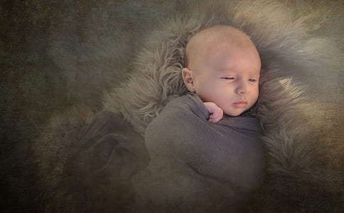 baby sleeping in brown fur textile