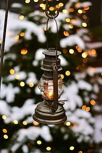 gray kerosene lamp hanged on black metal hook