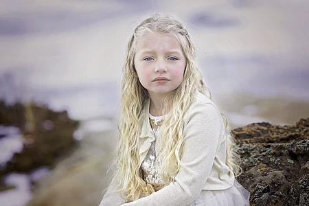 blonde girl sitting on rock