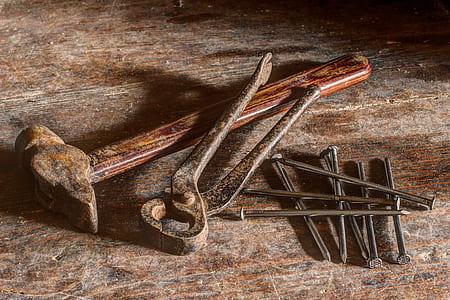 brown hammer, black tong, and gray nails