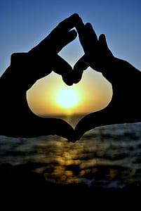 silhouette of two hands forming heart behind sunset