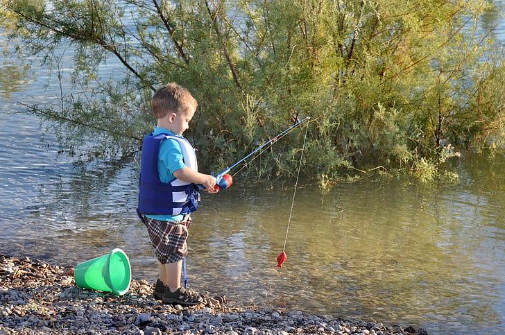 boy fishing in body of water