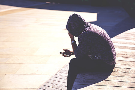 A man wearing a hoodie checks his mobile iPhone smartphone in an urban setting