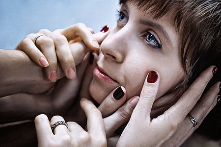 photo of hands touching woman's face