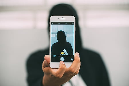 person wearing black top holding iPhone 6 taking picture