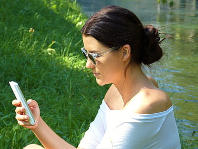 woman using smartphone near river