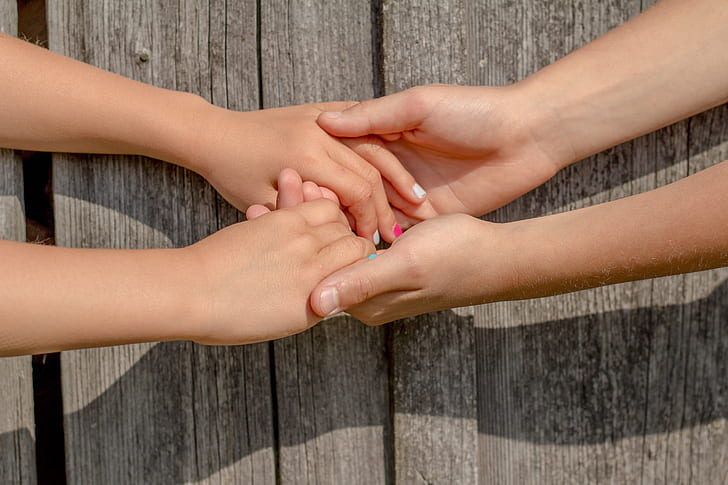 two people holding hands together beside gray wooden board