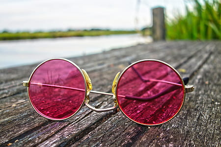 round silver-colored pink tinted sunglasses on grey wooden board