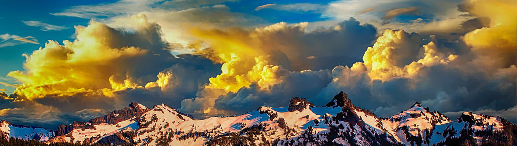 snowy mountain range and yellow clouds at daytime