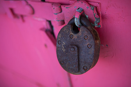 Close-up shot of a rusty lock captured against a vivid pink background