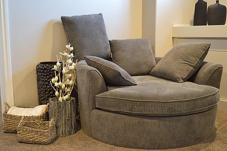 grey fabric chair near white wall paint