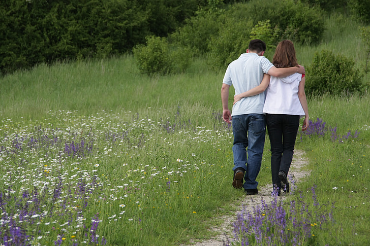 man and woman walking on grass field