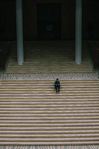 man sitting on beige stair