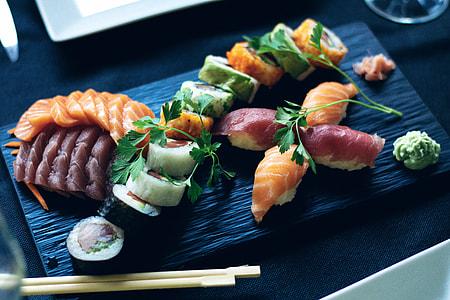 sushi on black board beside chopstick