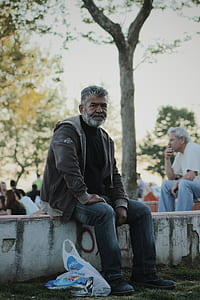 Man Wearing Gray Jacket Sitting on White Stone in Park during Day Time