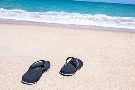 pair of black flip-flops in seashore