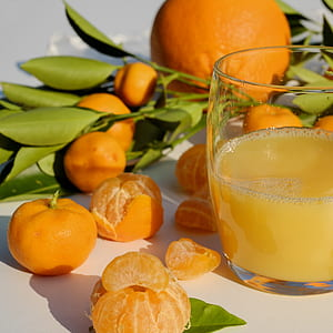 bunch of oranges near filled clear drinking glass