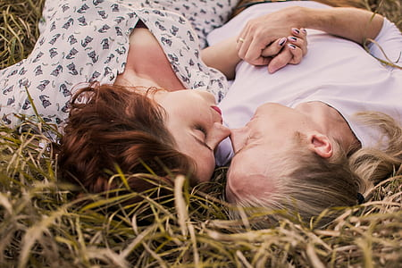 two woman lying on green grasses