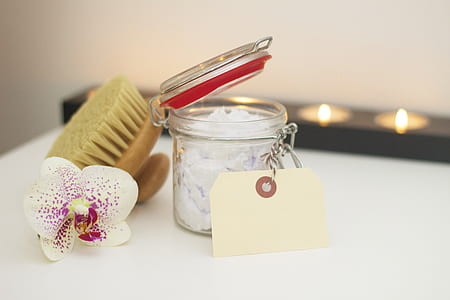 clear glass container, white and purple orchid flower, and brush