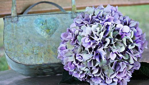purple and green flower bouquet near green and blue floral handbag