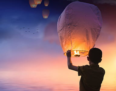 person holding floating lantern under sunset